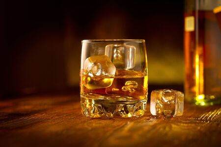 Whisky z kostkami lodu. Szklanka whisky i butelka na drewnianym stole na ciemnym tle. Szklanka alkoholu rumowego z bliska. Zbliżenie koniaku, napój spirytusowy, koktajl Zdjęcie Seryjne