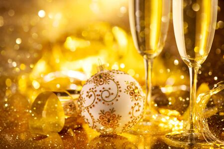 Holiday Champagne Flute over Golden glow background. Christmas and New Year celebration. Two Flutes with Sparkling Wine over Holiday Bokeh Blinking Background. Table setting, decoration