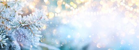 Árbol de Navidad con nieve decorado con guirnaldas de luces, vacaciones festivas Foto de archivo