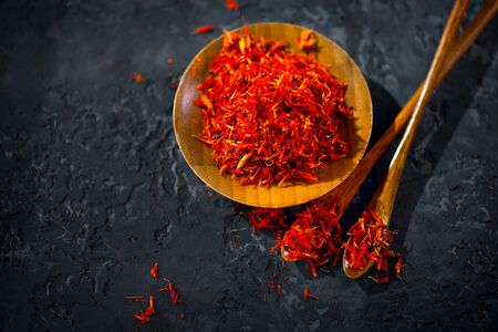 Saffron Spice. Saffron spices on black stone table in a wood bowl and a spoon. Spice and herbs on slate background. Seasonings, condiments. Cooking ingredients, flavor