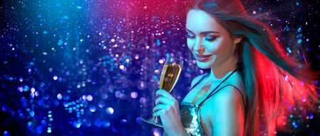 Model girl with glass of champagne drinking and dancing at disco party