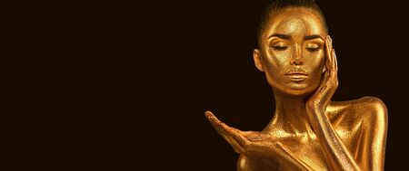 Fashion art Golden skin Woman face portrait closeup. Model girl with holiday golden Glamour shiny makeup. Sequins. Gold jewellery, jewelry, accessories. Beauty gold metallic body, Lips and Skin