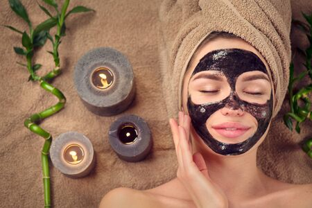 Beautiful woman with black purifying black charcoal mask on her face. Beauty model girl with black facial peel-off mask lying in spa salon. Skin care, acne treatment, cleansing skin. Peel. Top view