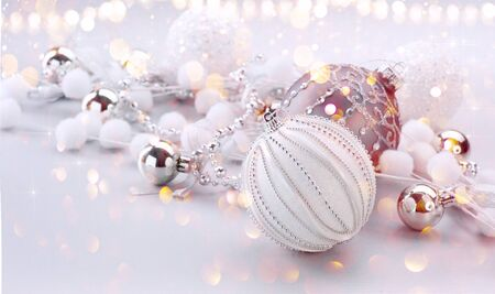 Silver Color Christmas and New Year Decoration on blurred grey background with lights. Border art design, holiday bauble. Beautiful Christmas ball closeup decorated with tinsel. Space for your text