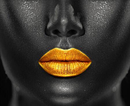 Lips Makeup art, black skin and Gold lips, golden lipgloss on sexy lips, golden lipstick. Beautiful model girl's mouth, black skin. Make-up. Beauty dark face makeup close up. African American closeup