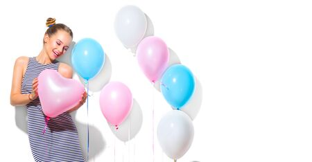 Beauty girl with colorful air balloons laughing over white background. Beautiful Happy Young woman on birthday holiday party. Joyful model having fun, playing, celebrating with pastel color balloon Archivio Fotografico