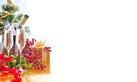 Celebrazione di Natale e Capodanno con champagne. Tavolo per la cena delle vacanze con decorazione dell'albero di Natale, confezione regalo, due flauti di spumante sul tavolo servito, cena di Natale per le vacanze. Champagne