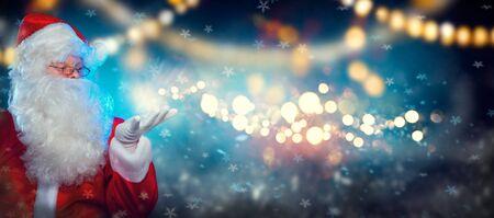 Santa Claus con regalo mágico en sus manos. Retrato de feliz Santa Claus haciendo magia en la noche, soplando estrellas mágicas de Navidad, apuntando con la mano sobre el fondo de la noche de vacaciones Foto de archivo