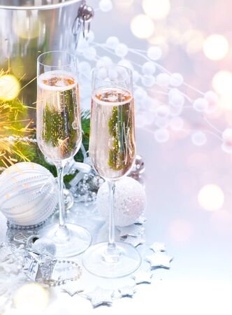 Christmas and New Year celebration with champagne. Holiday dinner table setting with Christmas tree decoration, two flutes of sparkling wine on served table, holiday Xmas dinner. Champagne