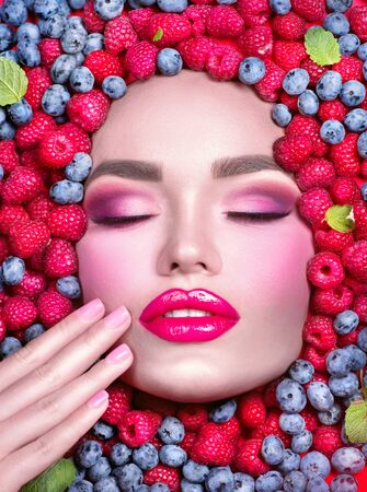 Beauty fashion model girl lying in fresh ripe fruits, berries and mint. Face in colorful berries close-up. Beautiful make-up, juicy and sexy lips, pink eyeshadows. Healthy eating concept, facial mask