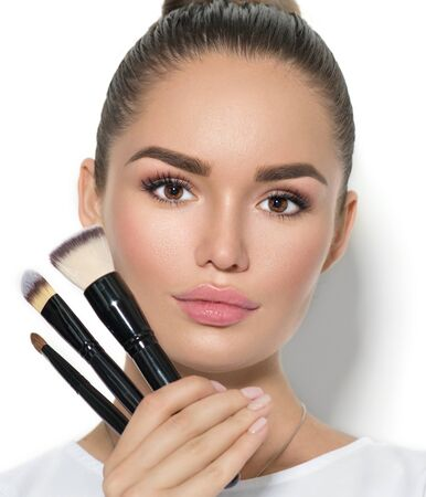 Beauty model girl, makeup artist holding set of make up brushes and smiling. Stock Photo