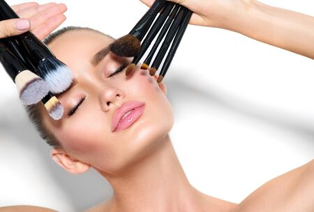 Beauty model girl, makeup artist holding set of make up brushes closeup.