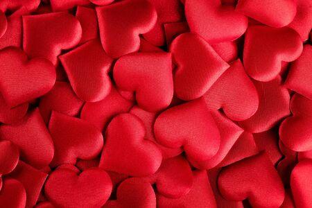 バレンタインデーの背景。赤いサチンの心と休日の抽象的なバレンタインの背景。ハートシェイプの背景。ラブコンセプト
