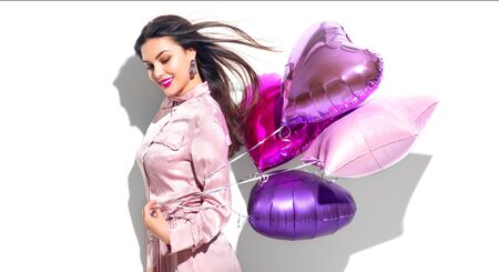 Valentine Beauty girl with colorful heart air balloons laughing, isolated on white background. Beautiful Happy Young woman. Holiday birthday party, having fun, celebrating with pink color balloon