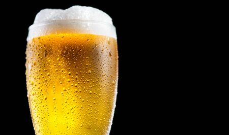 Beer. Cold Craft light Beer in a glass with water drops. Pint of Beer close up isolated on black color background. Ale beer Border design. Closeup Imagens