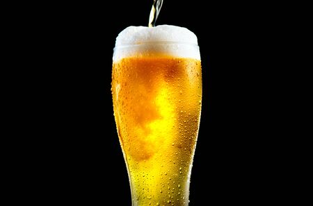 Beer. Cold Craft light Beer pouring in a glass with water drops. Pint of Ale Beer close up isolated on black background, closeup. Pub, bar menu concept Stock Photo