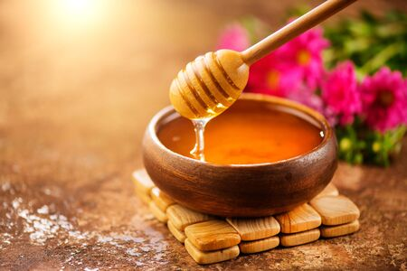 Honey dripping from honey dipper in wooden bowl.