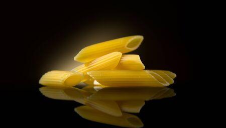 Pasta Penne on dark background. Italian mediterranean food, diet, dieting. Cooking Italian pasta penne close-up, on dark background Zdjęcie Seryjne