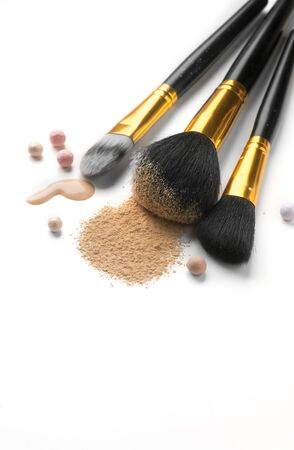 Cosmetic liquid foundation or cream, loose face powder, various brushes for apply makeup. Make up concealer smear and powder isolated on a white background. Products for Perfect face skin makeup.