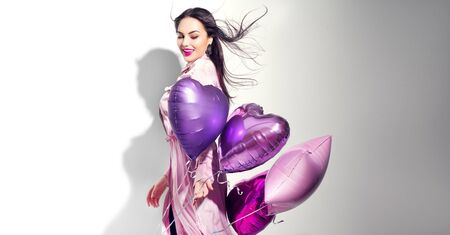Valentine Beauty girl with colorful heart air balloons laughing, isolated on white background. Beautiful Happy Young woman. Holiday birthday party,  having fun, celebrating with pink color balloon.