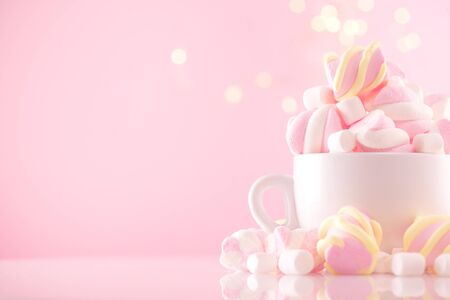 Marshmallow. Close-up of Marshmallows colorful chewy candy, over pink bokeh background, closeup. Sweet holiday food dessert in a cup with hot chocolate close-up. Candies