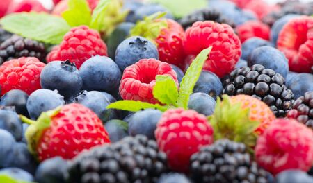 Berries. Various colorful berries background. Mint leaves, Strawberry, Raspberry, Blackberry, Blueberry close-up backdrop. Fresh Bio Fruits, Healthy eating, diet, dieting concept, organic food. Zdjęcie Seryjne