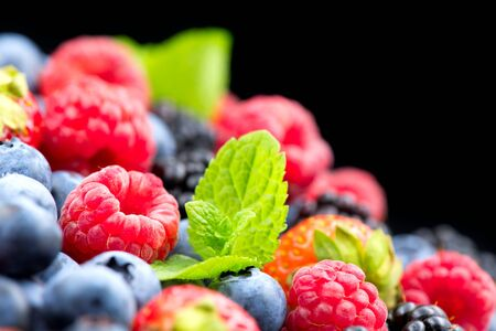 Berries. Various colorful berries background. Mint leaves, Strawberry, Raspberry, Blackberry, Blueberry close-up backdrop, isolated on black. Bio Fruits, Healthy eating, diet Zdjęcie Seryjne