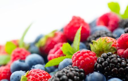 Berries. Various colorful berries background. Mint leaves, Strawberry, Raspberry, Blackberry, Blueberry close-up backdrop, isolated on white. Border label design.Bio Fruits, Healthy eating, diet Zdjęcie Seryjne