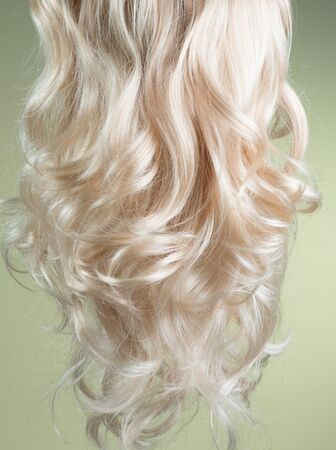 Blond Hair. Beautiful healthy long curly blonde hair close-up texture. Dyed Wavy white hair background, coloring, extensions, cure, treatment concept. Over green backdrop. Haircare
