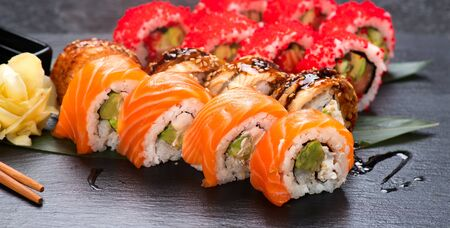 Sushi with chopsticks. Sushi roll japanese food in restaurant. California Sushi roll set with salmon, vegetables, flying fish roe and caviar closeup. Japan restaurant menu 写真素材