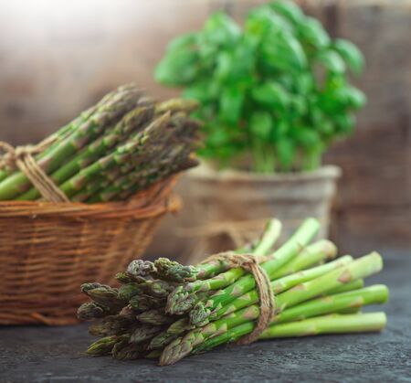Asparagus. Fresh raw organic green Asparagus sprouts closeup. Over wooden table. Healthy vegetarian food. Raw vegetables, market