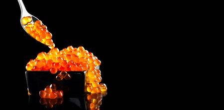 Red Caviar in a spoon. Caviar in bowl over black background. Close-up salmon caviar. Delicatessen. Gourmet food. Texture of caviar. Seafood isolated on black