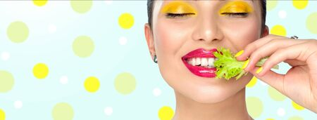 Healthy eating, diet. Beautiful healthy girl eating raw vegan food and smiling. Beauty young fashion woman eats green fresh lettuce salad leaf, organic vegetables. Vegetarian concept. Makeup.