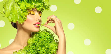 Healthy eating, diet. Beautiful healthy girl eating raw vegan food and smiling. Beauty young fashion woman eats green fresh lettuce salad leaf, organic vegetables. Vegetarian. On green background