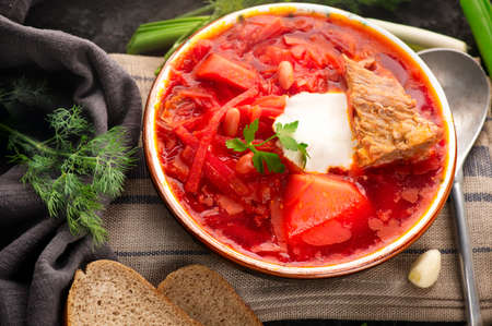 Traditional Ukrainian Russian borscht with white beans on the bowl. Plate of red beet root soup borsch on black rustick table. Beetroot soup Top view. Traditional Ukraine food cuisine.