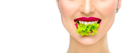 Healthy eating, diet concept. Beautiful healthy girl eating raw vegan food and smiling. Lips. Beauty young fashion woman eats green fresh lettuce salad leaf, organic vegetables. Vegetarian. Makeup Standard-Bild