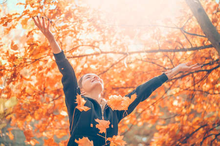 Autumn model girl spinning and laughing in autumnal park, forest, throws colorful leaves. Beautiful Young Woman Having Fun outdoors. Raising hands. Falling Red and Yellow Leaves. Healthy Lifestyle.