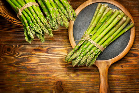 Asparagus. Fresh raw organic green Asparagus sprouts closeup. On wooden table background. Healthy vegetarian food. Raw vegetables, market. Healthy eating concept, diet, dieting. Top view, flat lay