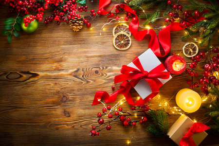 Christmas Gifts on wooden background, beautiful Xmas and New Year backdrop with colorful wrapped gifts box, baubles, candles and lighting garland over wood table background. Top view, flatlay, frame