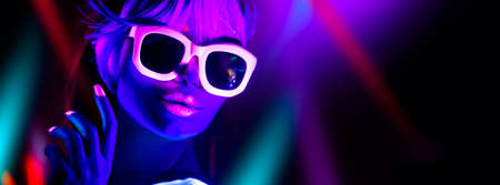 Disco girl in neon light dancing in night club. Fashion model woman. Closeup portrait of beautiful girl with fluorescent make-up. Body Art design in UV. Sunglasses. Colorful make up Standard-Bild