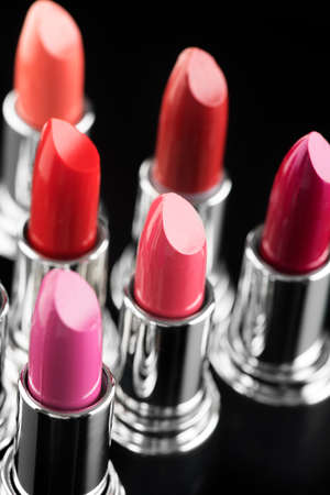 Lipstick. Fashion Colorful Lipsticks over black background. Lipstick tints palette, Professional Makeup and Beauty. Beautiful Make-up concept. Lipgloss. Vertical image