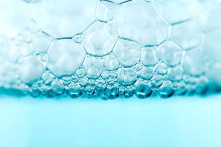 Foam. Soap foam popping bubbles background. Soap sud macro structure. Soap foam close-up, blue background.