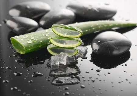 Aloe Vera slices and spa stones closeup. Aloevera plant leaf gel, natural organic renewal cosmetics, alternative medicine. Skin care concept. Skincare. Moisturizing. On black background Stock Photo