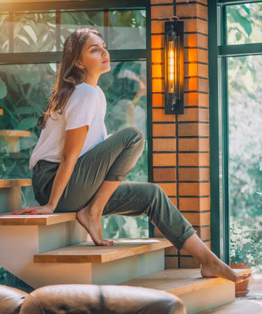Young woman sitting on a stairs and posing. Cosy room in big house, interior design. Beauty model girl portrait