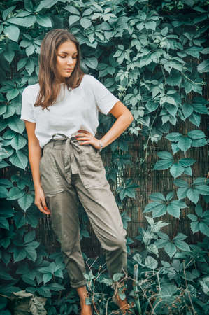 Young woman posing outdoor. Urban Fashion style look. Beauty brunette model girl over green leaves background. Casual wear