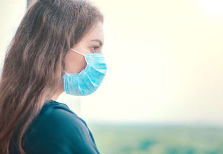 Young woman wearing her protective mask and breathes in clean air.  Coronavirus, Covid-19 flu virus protection. Beautiful happy girl outdoor. Pollution protect. Standard-Bild