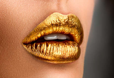 Golden lipstick closeup. Metal gold lips. Beautiful makeup. Sexy lips, bright paint on beautiful model girl's mouth, close-up. Metallic Lipstick closeup. Isolated on black background