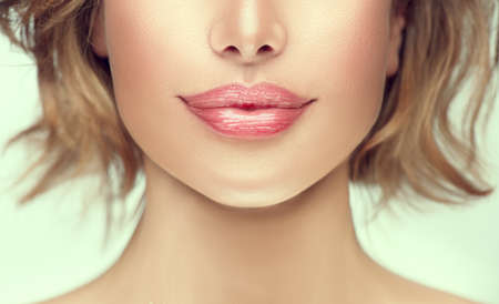 Beautiful young woman's lips closeup. Plastic surgery, fillers, injection. Part of the model girl face, youth concept. Perfect healthy skin. Natural make-up. Chin. Youth and beauty. Health care Standard-Bild
