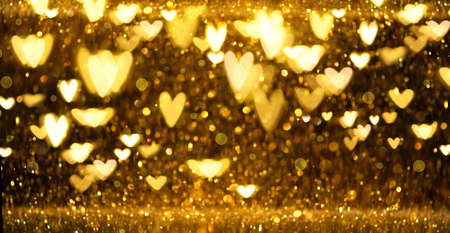 Christmas Gold glowing Background. Golden Holiday Abstract Glitter Defocused Backdrop With Blinking Stars and hearts. Gold Bokeh on black background. Festive defocused elegant border Standard-Bild