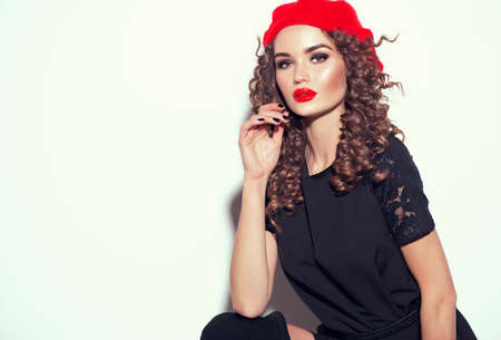 Beautiful young woman posing in studio in black dress and red beret. Beauty model girl portrait. Trendy outfit. Beautiful brunette female with curly hair style, red lips, perfect make-up